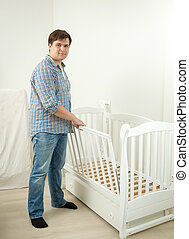 Expectant father assembling bed for his future baby - Young...