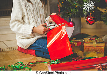 Closeup of girl sitting under Christmas tree and cutting red...