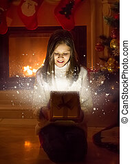 Portrait of cute girl opening box with Christmas present....
