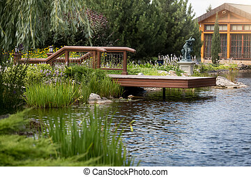 Beautiful wooden pier on pond luxurious mansion