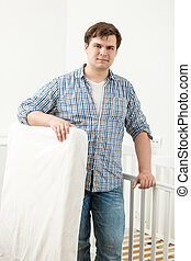 Portrait of handsome man posing at baby's cot with new...