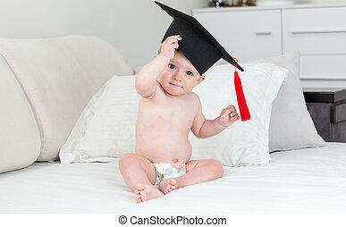 Adorable 10 months old baby in black graduation cap with tassel