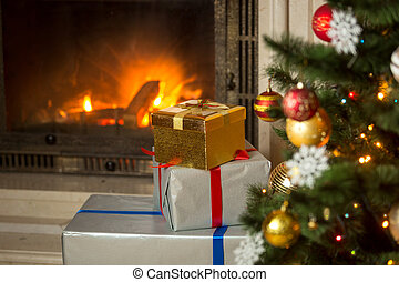 High stack of Christmas presents at house with burning fireplace