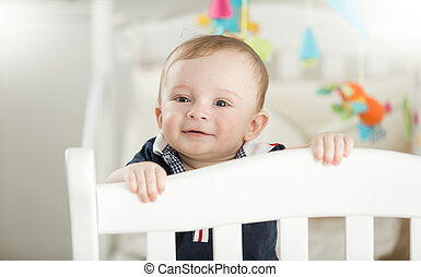 Smiling 9 month old baby standing in white wooden crib -...