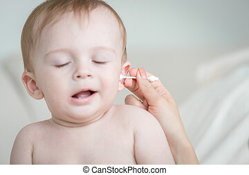Closeup of mothers hand cleaning her baby's ear with cotton...