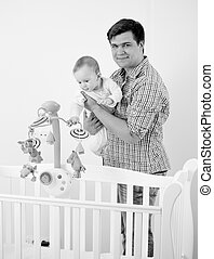 Black and white portrait of father showing his baby new cot...