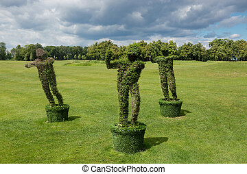 Beautiful bushes at park trimmed in form of satyrs - Three...