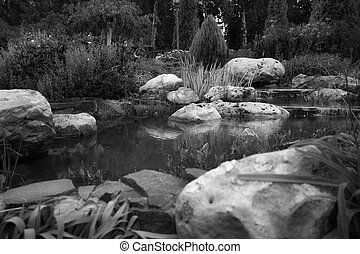 Black and white image of beautiful pond with big boulders in...