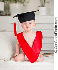 Portrait of adorable baby boy in graduation cap and collar sitting on bed