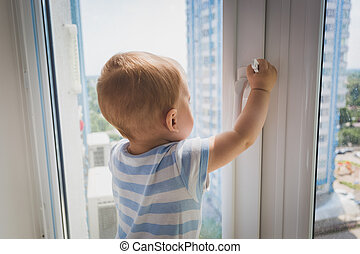 Cute baby boy pulling by the window handle. Concept of child...