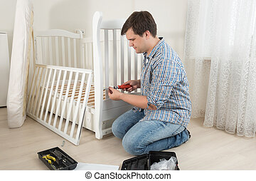 Young man assembling baby's crib in nursery