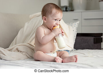 9 months old baby boy sitting on bed and drinking milk from bottle