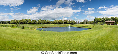 Panorama of golf course with pond in sunny day - Panorama of...
