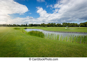 Beautiful view of golf course with water hindrance at sunny...