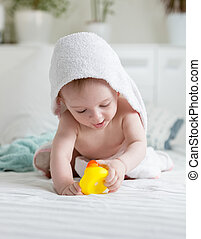 Portrait of happy baby in hooded towel playing with yellow...