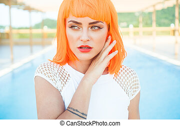 Creative look of sexy woman in orange wig by the pool