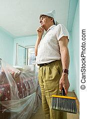 Senior man thinking about redecorating, holding large...