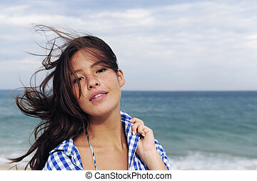 wind: woman with tousled hair at the sea - young woman at...