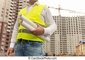 Toned image of construction engineer holding blueprints -...
