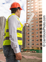 Building inspector pointing at building under construction