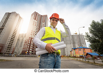 Young engineer standing at new buildings with blueprints -...