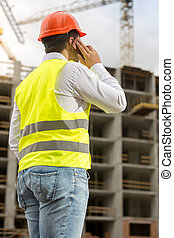 Rear view of businessman in hardhat and safety vest talking by phone at construction site