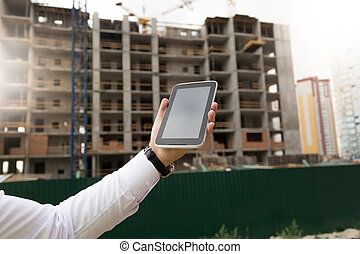 Closeup image of male hand holding digital tablet with building site on background