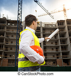 Rear view image of young engineer pointing at building with...