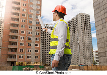 Architect in hardhat pointing with rolled blueprints at building under construction