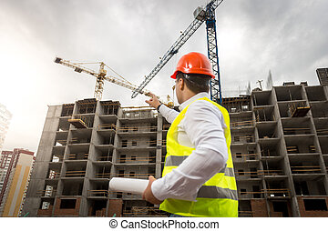 Portrait of architect holding blueprints and pointing at...