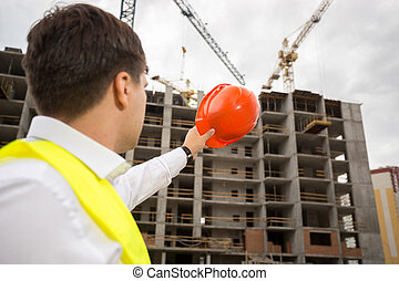 Young construction engineer pointing at building under...