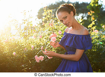 Beautiful girl relaxing in a rose garden - Beautiful girl in...