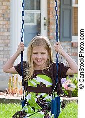 Girl Swinging - Little Girl Swinging in Front of Her House