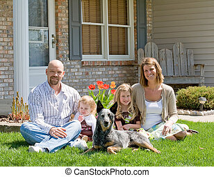 Family at Home - Family Sitting in Front of Their Home
