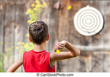 Child playing darts - Young boy playing darts outdoor