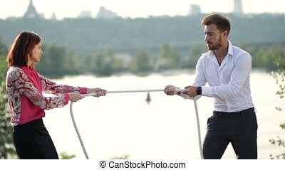 Business partners playing tug of war outdoors - Businessman...