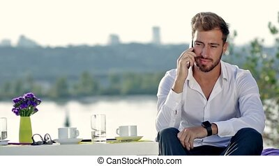Handsome man talking on the phone outdoors - Handsome man...