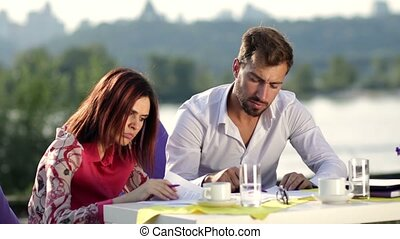 Two business partners signing a contract outdoors - Two...