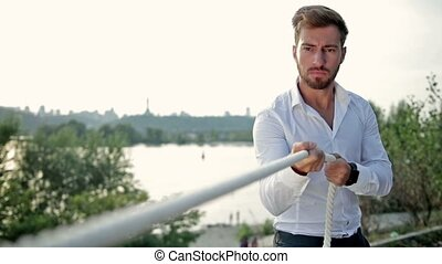 Young businessman pulling a rope outdoors - Young...