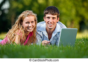 A couple relaxing in the park with a laptop, lying on the...