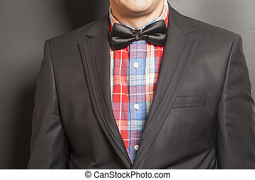 Man wearing a black suit and black bow tie