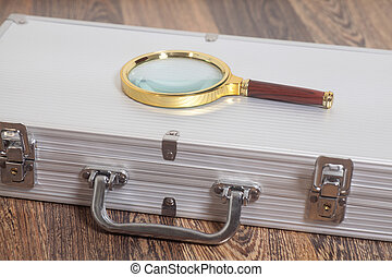 Magnifying glass on silver suitcase on wooden background