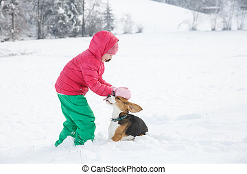Little girl playing with her dog in a snowy landscape,...