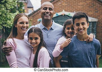 Happy Family Outdoors - Happy family posing outdoors. The...