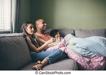 Family Film Time - Father curled up on the sofa with his two...