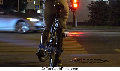 Female biker crossing evening street. Traffic light and...