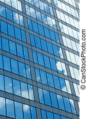 glass office building facade - Clouds and sky reflection on...