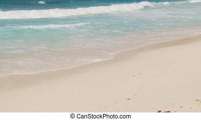 closeup of whitecaps on sandy beach - closeup of waves...