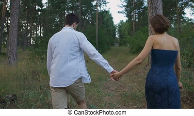 A pleasant man with a beard leads his beautiful wife or girl on a footpath in the woods.