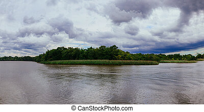 Thunderclouds over the river in the spring. The strong wind...